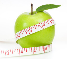 Dieting concept Green apple with measuring tape on white backgro