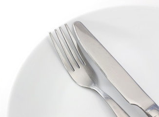 White plate, fork and knife on light background
