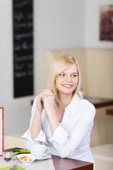 junge blonde frau sitzt im café
