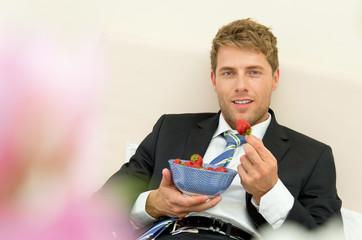 Mann isst Erdbeeren