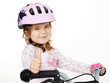Cute girl with bicycle helmet shows thumb up