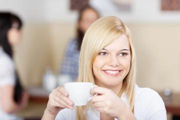 junge blonde frau trinkt kaffee