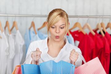 frau schaut überrascht in einkaufstüte