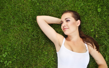 Beautiful young girl lying on the grass
