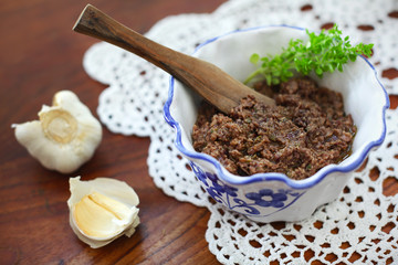 Tapenade appetizer with basil and garlic in a rustic bowl