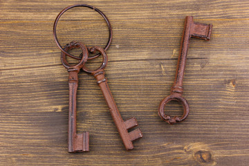 a bunch of antique keys on wooden background