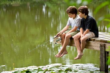Zwei jungendliche Freunde angeln am idyllischen Teich