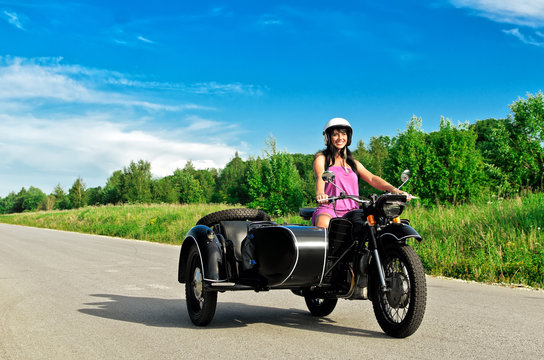Pretty woman riding a motorcycle with a sidecar.