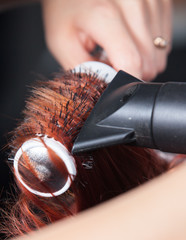 hair stylist with blower work on woman hair in salon