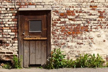 Dilapidated door in an old brick wall