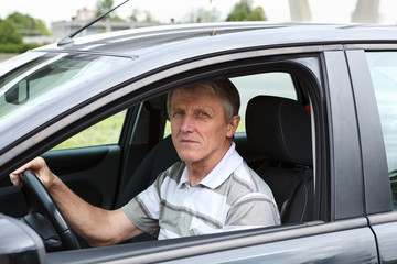 Serious mature man in car on driver seat and holding wheel
