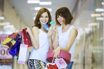 Two girls with packages show credit cards