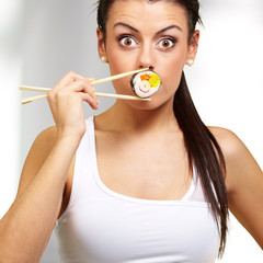 young woman covering her mouth with a sushi piece, indoor