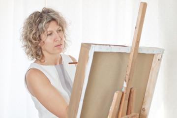 Beautiful artist paints a picture.