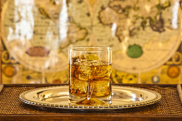 whisky glass on silver platter on wooden table with ancient worl