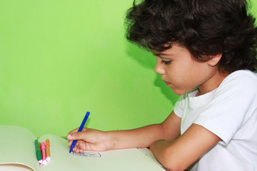 Little curly boy is drawing with colored pencils at home
