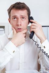 Mann am Telefon denkt nach