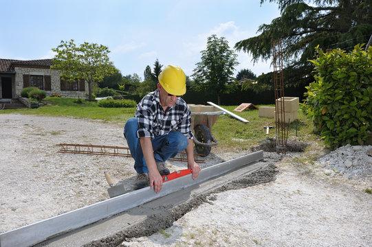 un ouvrier maçon qui nivelle du béton
