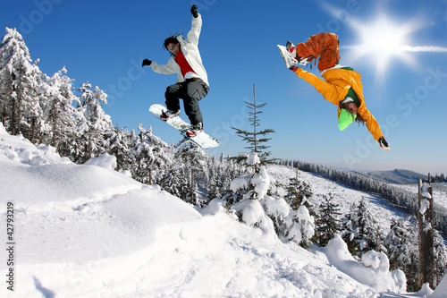 Wall mural Snowboarders jumping against blue sky