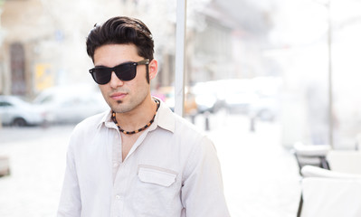 attractive man wearing sunglasses looking cool on the street