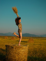 happy, young woman jumping on hay stack