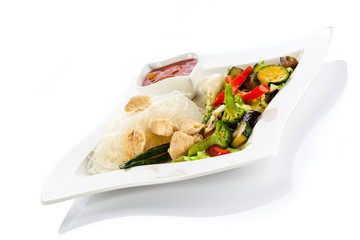 Roasted meat, rice noodles and vegetables on white background