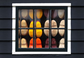 Wooden souvenir clogs behind a window of an old Dutch house
