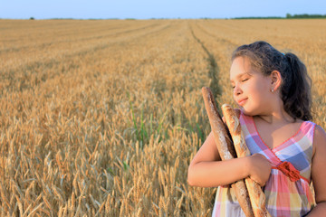 Girl with bread in the wheat field
