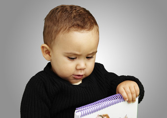 portrait of kid holding notebook over grey background