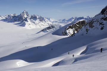 Montée à ski sur pente crevassée et paysage glaciaire infini.