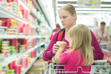 Mother and daughter shopping in milk section in supermarket