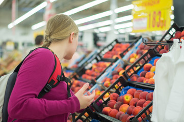 Woman choose red apples in supermarket