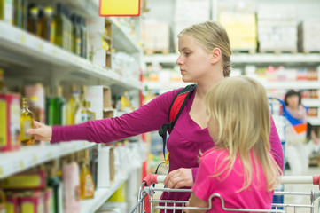 Mother and daughter shopping in oil section in supermarket