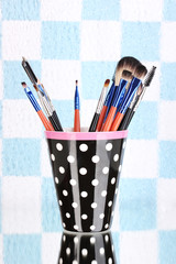 Makeup brushes in a black polka-dot cup on colorful background