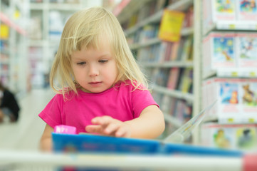 Adorable girl with interactive book on cart in supermarket