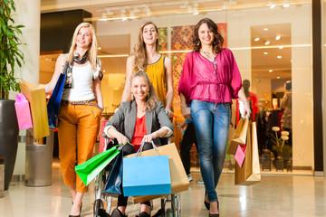 Vier Freundinnen beim Shoppen in einer Mall mit Rollstuhl