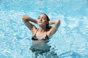 Junge Frau im Pool im Sommer