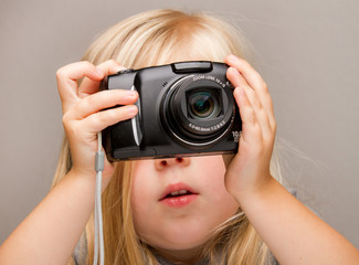Young child holding a camera taking a picture