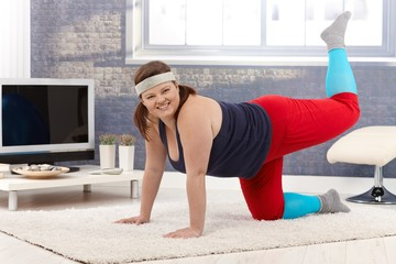 Happy woman doing gymnastics at home