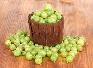 Green gooseberry in wooden cup on wooden background