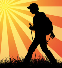 Hiker (backpacker) silhouette walking until sunset.
