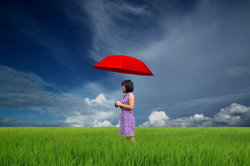 young woman with red umbrella in a green field under rain