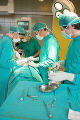 Serious surgeon team operating a patient