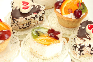 sweet cakes with fruits and chocolate isolated on white