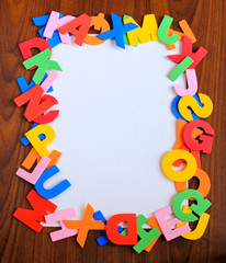 Colorful alphabet as frame with white paper on wooden background