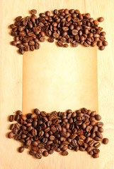 Coffee beans with old paper for notes on the wooden background