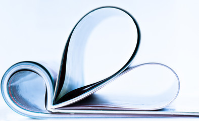 Pages of magazine curved into a heart shape