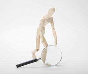 Wooden man with magnifying glass on white background