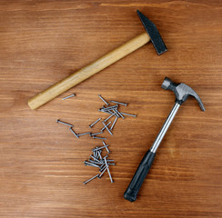 Hammers and metal nails on wooden background