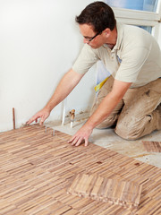 Carpenter at work is fitting wood parquet on the floor